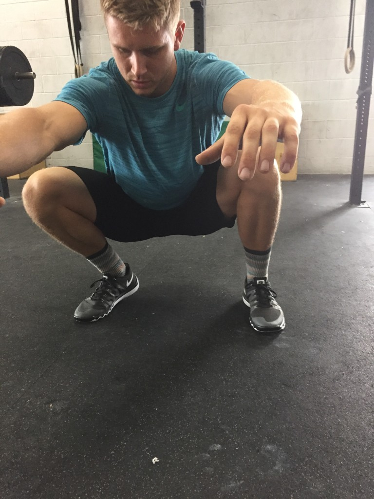 Coach Bryce demonstrating ankle mobility at CrossFit Invictus in San Diego