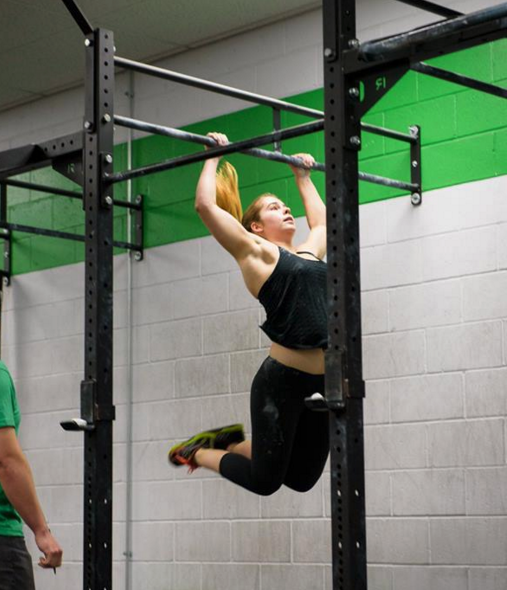 female athlete demonstrates butterfly pull-up exercise during CrossFit workout