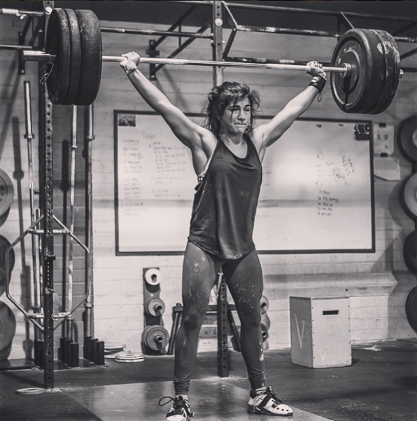 Lauren Fisher holds CrossFit power snatch lift position at top of exercise